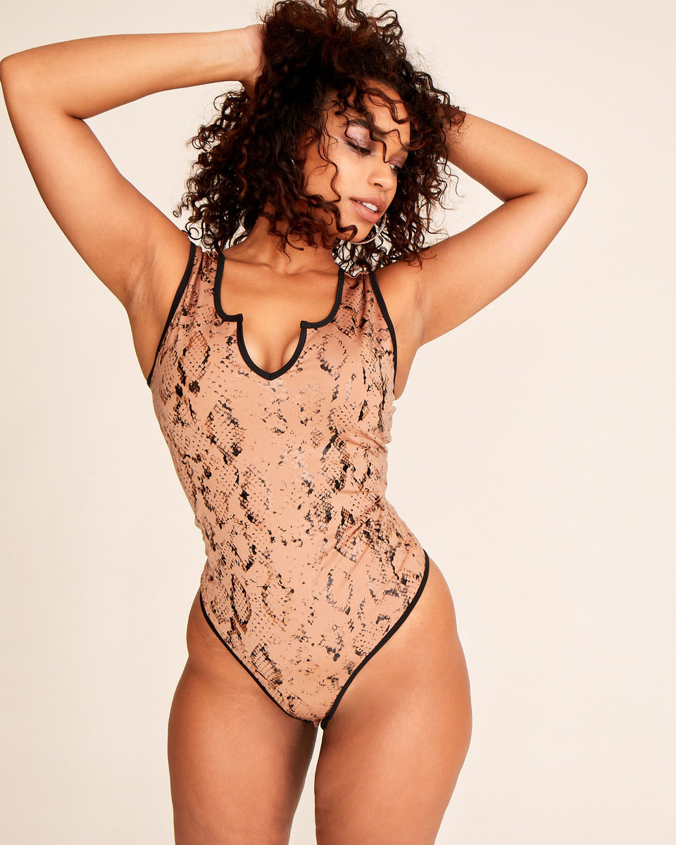 Nude python print stretch bodysuit with Baby Phat metal logo at the back Stretch fabric and tight fit. Notched neckline and snap closures.