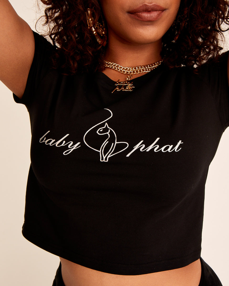 Short sleeved black cotton t-shirt with Baby Phat iridescent silver logo at the front. Soft, stretchy fabric and cropped, boxy fit.