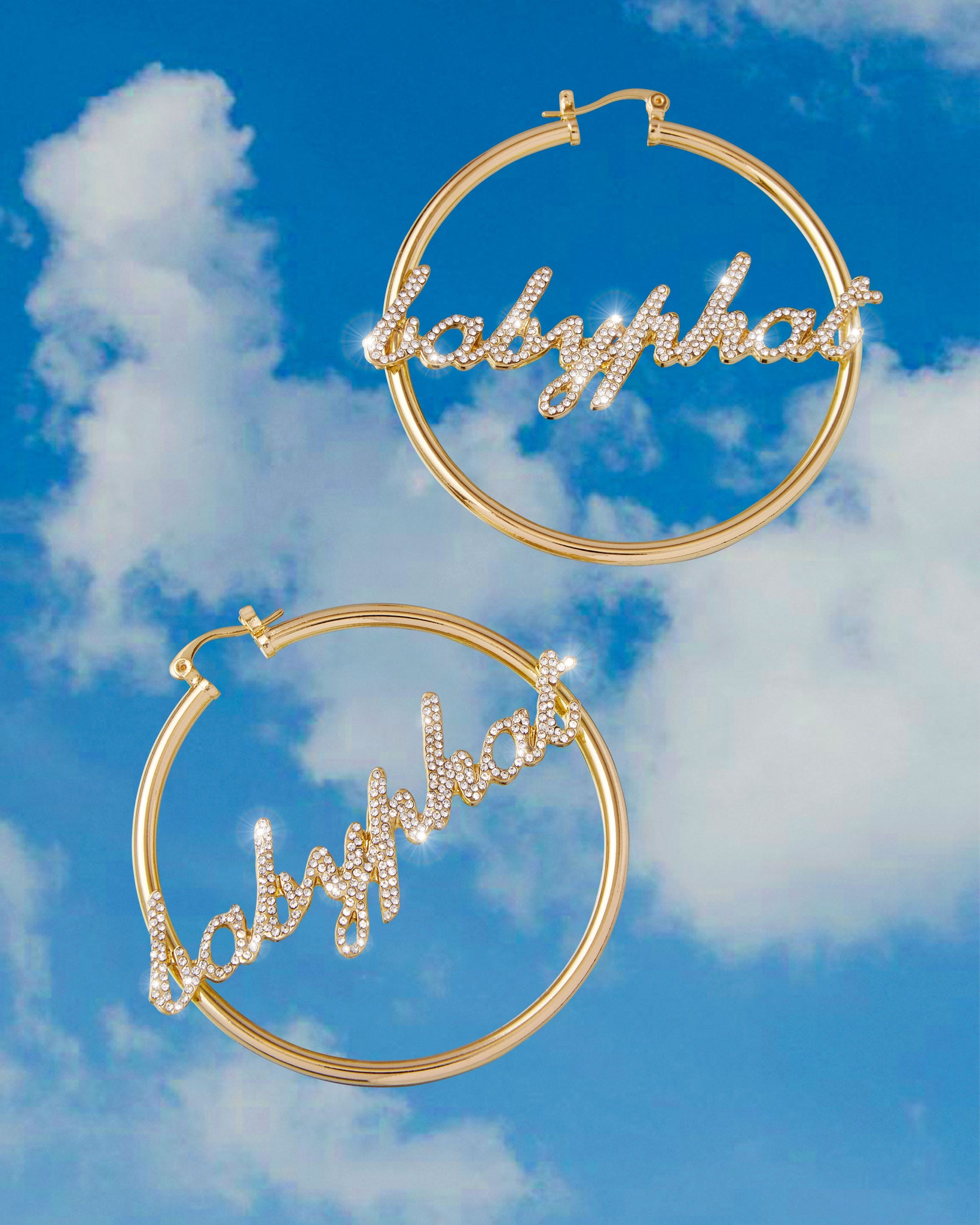 Baby Phat Pavé Script Nameplate Logo Hoops feature gold metal finish and pave crystal diamond detailing.