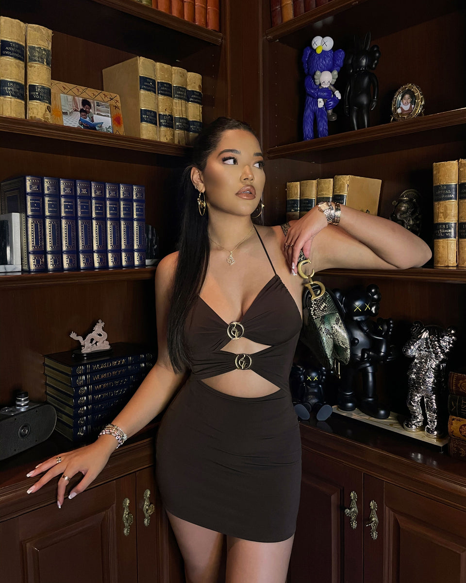 Ming Lee Simmons wears Baby Phat cutout dress in brown. Dress features gold metallic logo cat rings at the front.