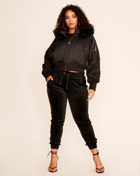 Black Baby Phat classic bomber jacket features hood with faux fur trim, front pockets, gunmetal zipper with cat logo charm. Arm pocket with gunmetal hardware.