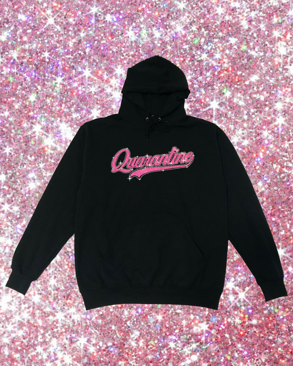 Black hoodie features pink glitter sparkle quarantine graphic at the front. Kangaroo pocket and drawstring hood. Wrist features Baby Phat cat logo in glitter.