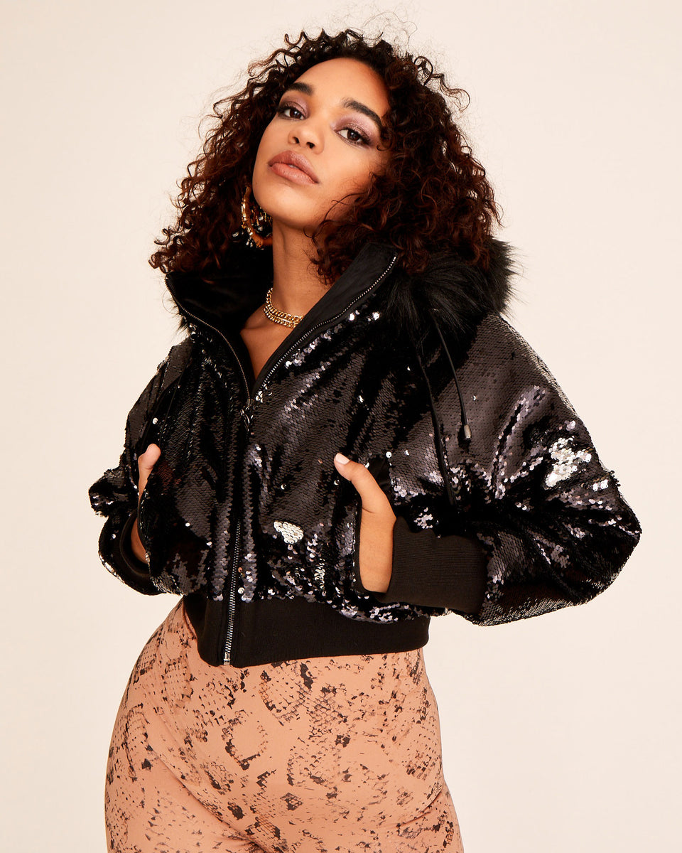 Black and silver Baby Phat 2-way sequin bomber jacket features hood with faux fur trim, front pockets, gunmetal zipper with cat logo charm. Ribbed waistband and cuffs. Features cat logo on the back.
