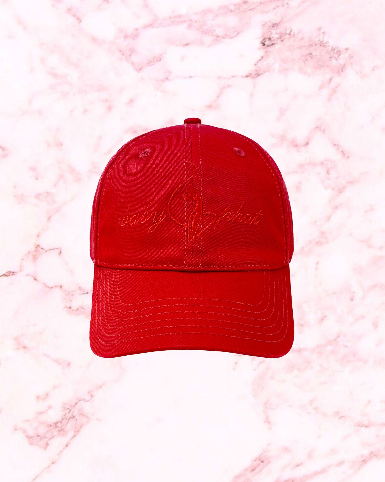 Red baseball hat features Baby Phat logo embroidered at front.
