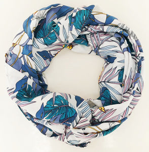 Travel scarf featuring hidden pocket in white tropical print