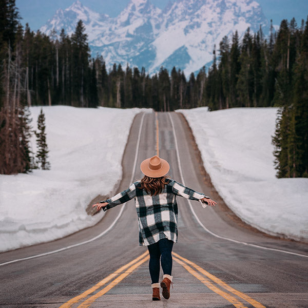 Girl wearing plaid shirt and cowboy hat, walking with arms open, down an empty road towards mountains, surrounded by evergreen trees.