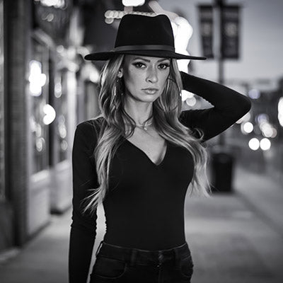 Black and white image of a girl wearing all black and black cowboy hat