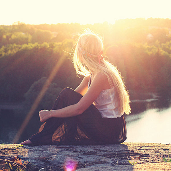 Girl sitting on a cliff watching the sunset over the valley.