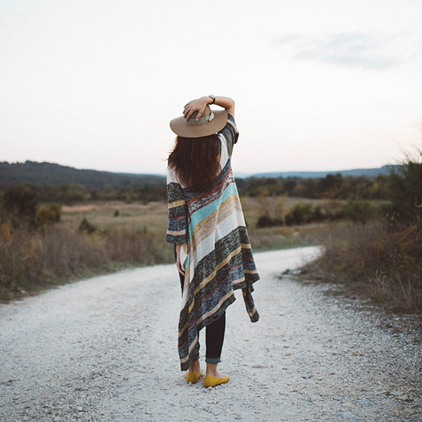 Girl standing, holding cowgirl hat on top of her head staring off into the distance, back turned