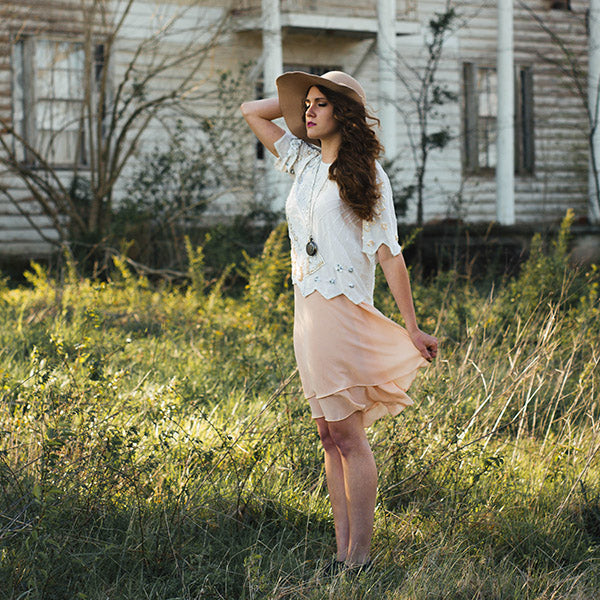 Girl standing in the grass with sun hat, wind blowing towards her