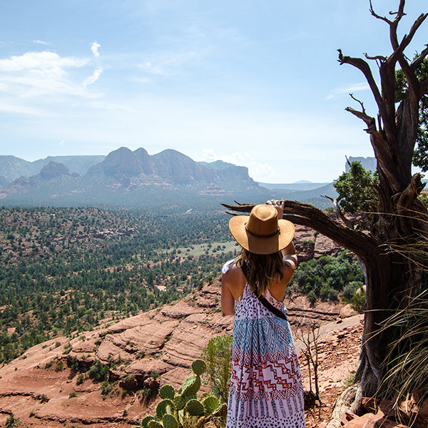 Back of girl wearing sunhat and sundress looking towards red rocks in Sedona