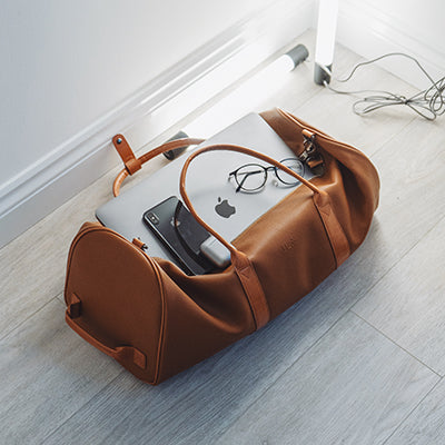 Brown duffle bag packed with laptop, phone, & glasses for travel.