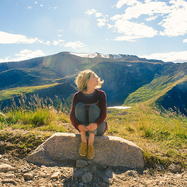 Girl sitting on a rock in a wide open fields and hills