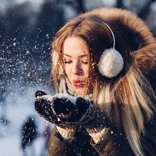 Girl blowing snow from her gloves