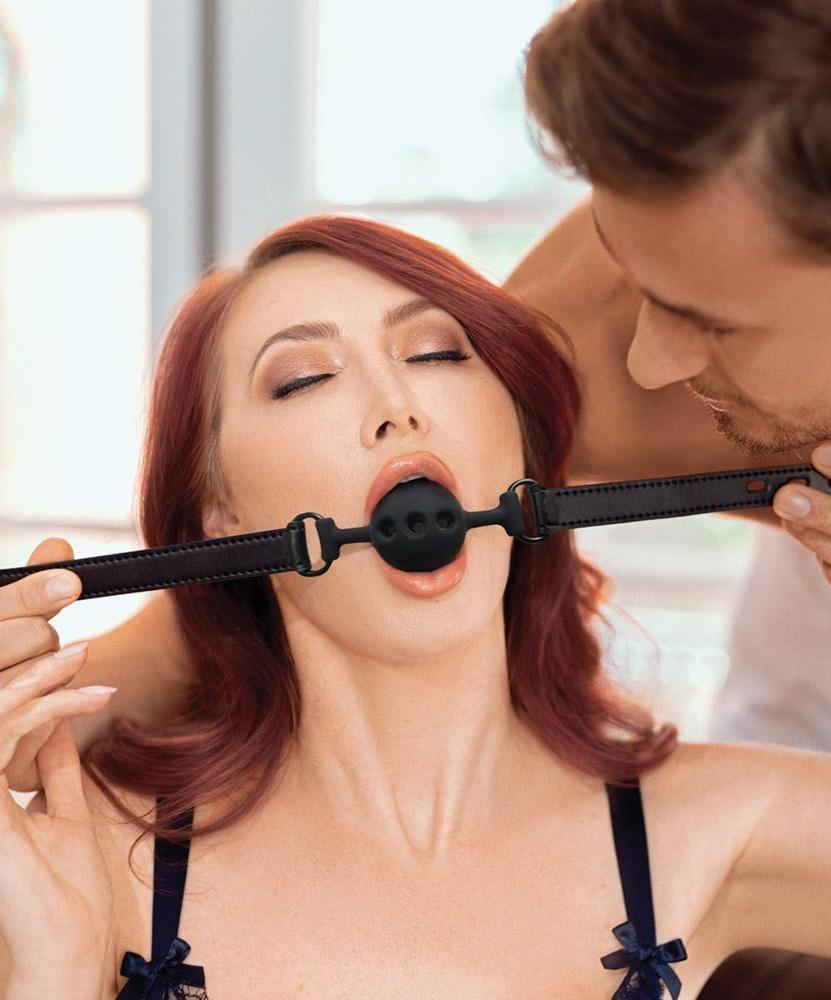 Saffron Vegan Leather Breathable Ball Gag by Sportsheets BEING PUT ON A REDHEADED MODEL BY A MAN