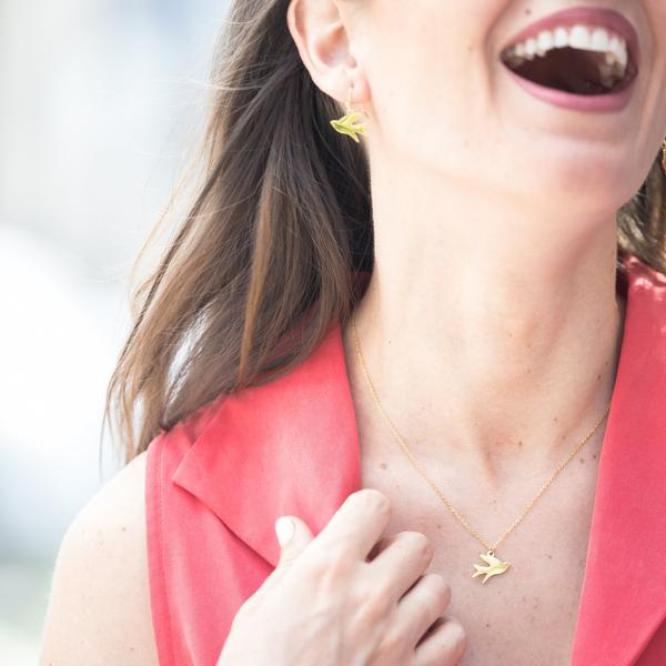 Woman wearing gold-plated bird necklace and earrings