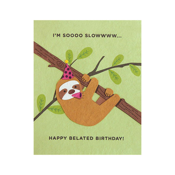 "Fair Trade handmade green card depicting a sloth hanging from branch wearing party hat and blowing party blower. Message reads ""I'm soooo slowwww... Happy belated birthday!"""
