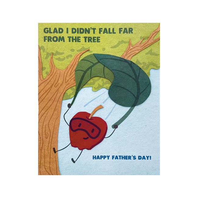 "Fair Trade handmade card depicting a red apple with a leaf-shaped parachute near a tree. Message reads ""Glad I didn't fall far from the tree. Happy Father's day"""
