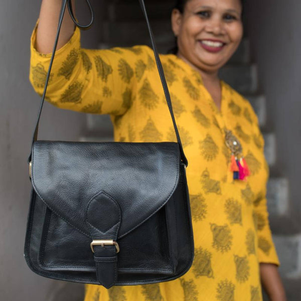 Black leather satchel with foldover front flap and buckle held by Indian artisan woman