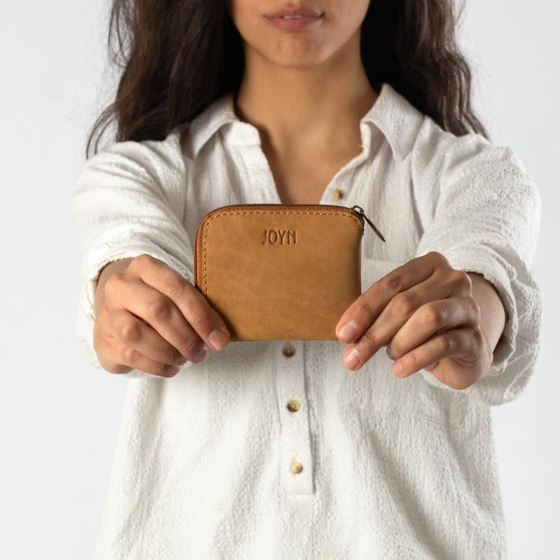 woman holding the Joyn Handmade leather zip up pouch – Shop Joyn Fair Trade and Vegan Handbags at ONLY JUST
