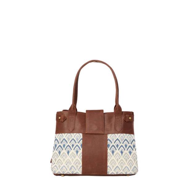Handbag with hand-blockprinted cotton with blue print and brown leather exterior with paddle handles and expandable side straps