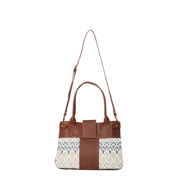 Handbag with hand-blockprinted cotton with blue print and brown leather exterior with paddle handles and expandable side straps shown with removable shoulder strap