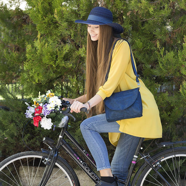 woman on a bike wearing Ava nylon bag by Smarteria - navy semi-circle foldover flap with navy nylon net body and adjustable long shoulder strap - Shop Fair Trade, Handmade, Ethical, Sustainable accessories & gifts Melbourne at ONLY JUST