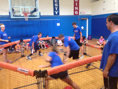 Camp counselors playing GaGa Ball game in school gym