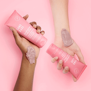 An overhead view of two hands holding the Sand and Sky Australian Pink Clay Flash Perfection Exfoliating Treatment.