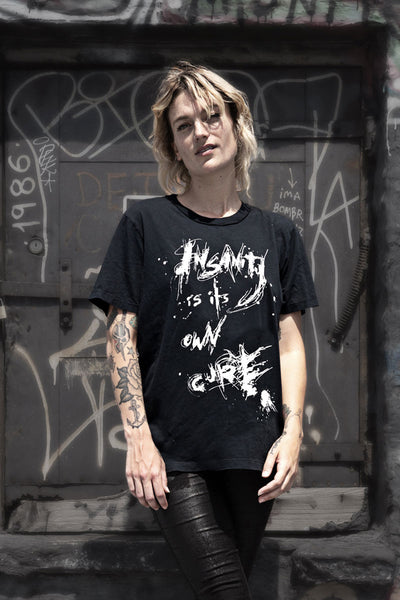 Woman wearing a black t-shirt with a graphic on the front that says Insanity is its Own Cure