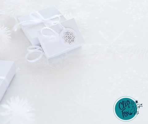 White gift boxes with ribbon on a white table clothe with silver snow flakes