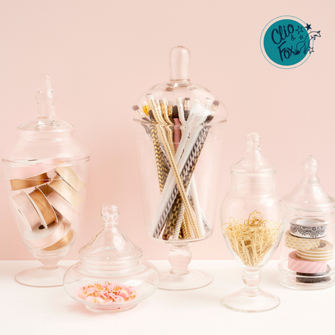 Vintage confectionary jars filled with office supplies against a blush pink background