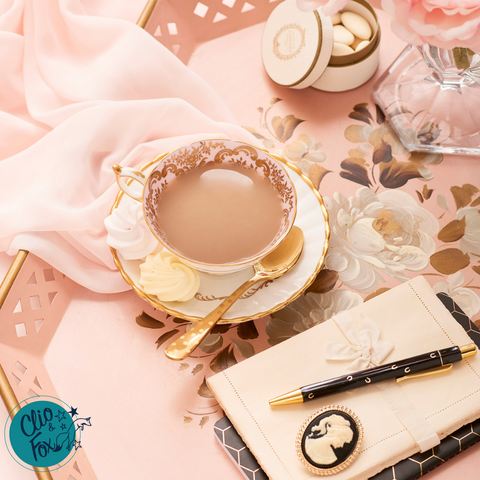 Pink vintage tea tray with blush pink chiffon scarf, vintage tea cup and saucer, black pen and notebook, with cream writing paper