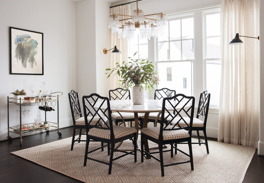 he light-filled dining area showcases a table from Four Hands, a light fixture by Arteriors, and faux bamboo Chinese Chippendale–style chairs from Ballard Designs
