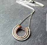 Mixed metal forged horse shoe layered pendant