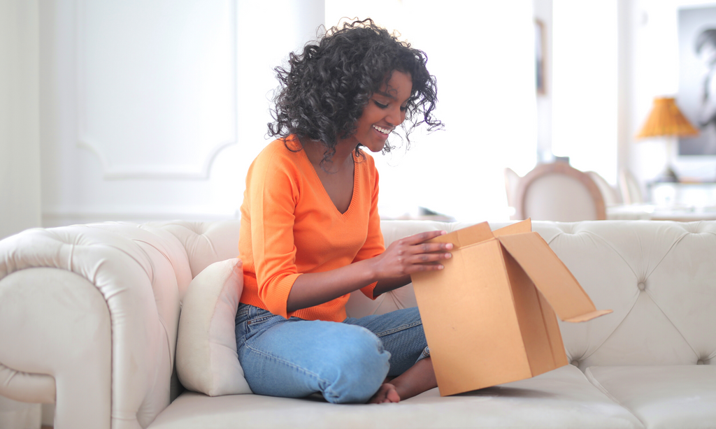 woman opening package, shipping FAQs