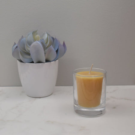 Citronella essential oil beeswax votive candle in a glass votive cup