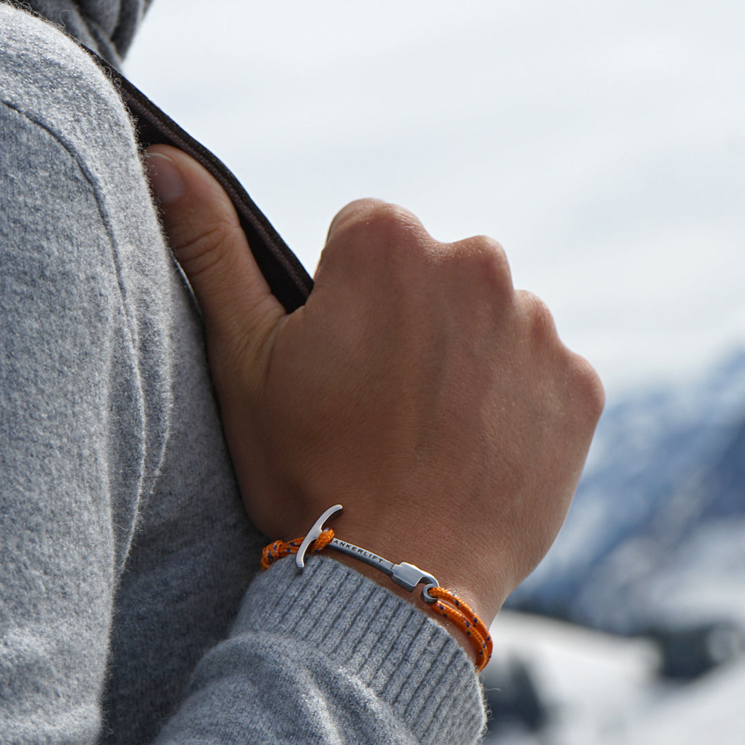 ANKERLIFT Armband orange Handgelenk vor Winterlandschaft