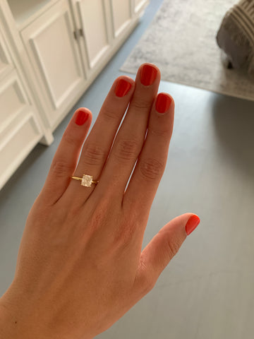 Hand wearing solitaire engagement ring with yellow band and cushion cut diamond