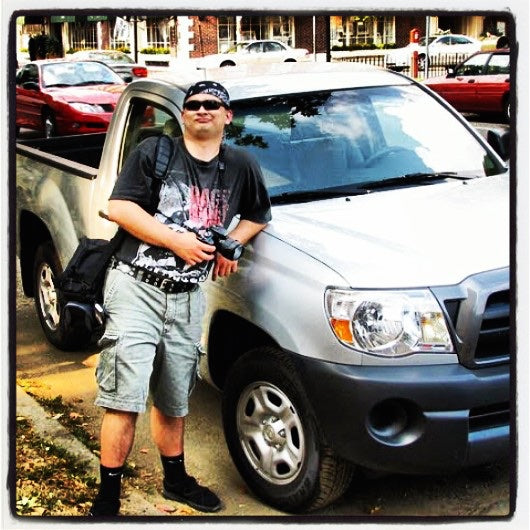 man wearing cargo shorts and flip flops with socks (????!) leaning against a Toyota Tacoma pickup truck and holding a camera. @ americanbogan.com