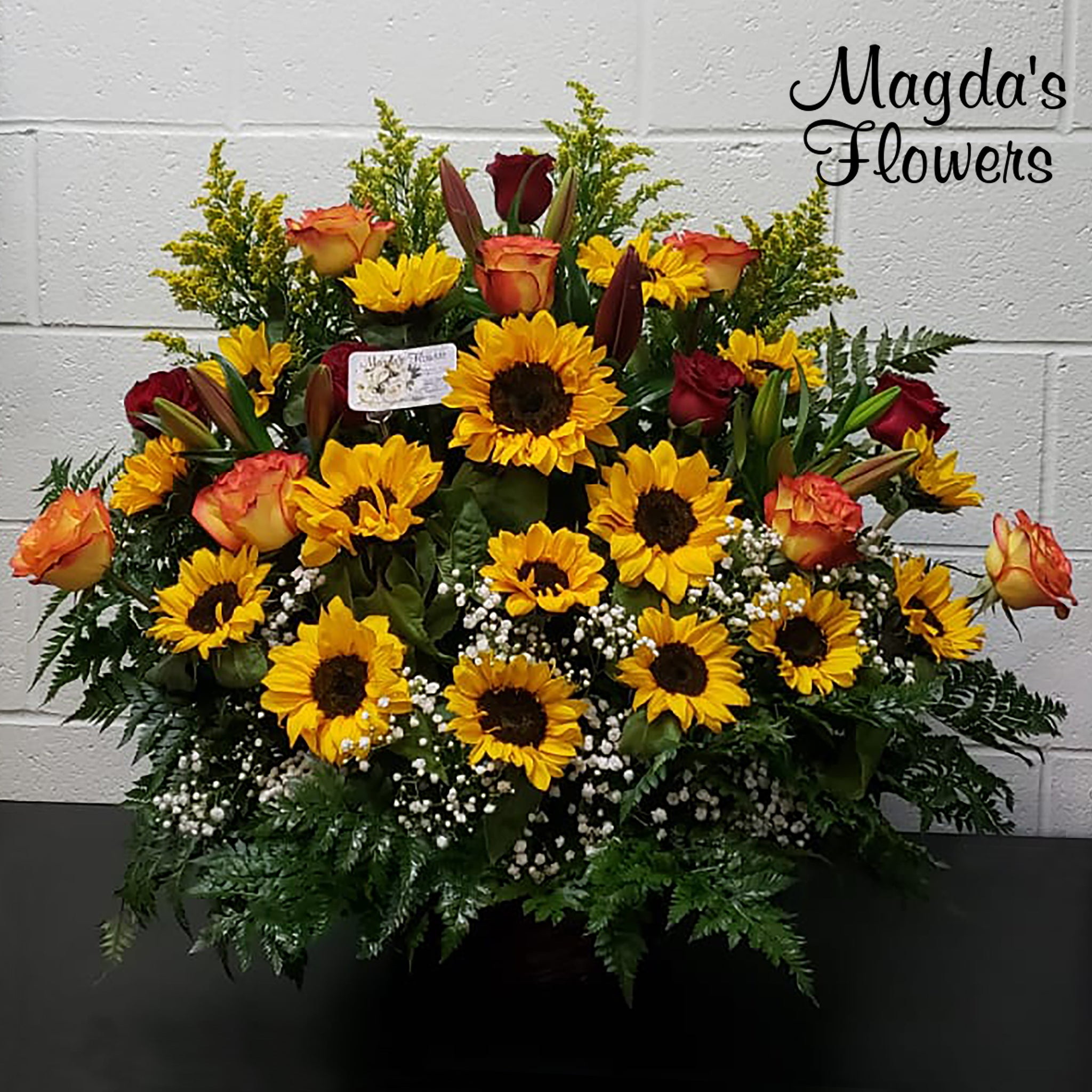 Beautiful sunflowers, roses and burgundy lilies in a large basket.
