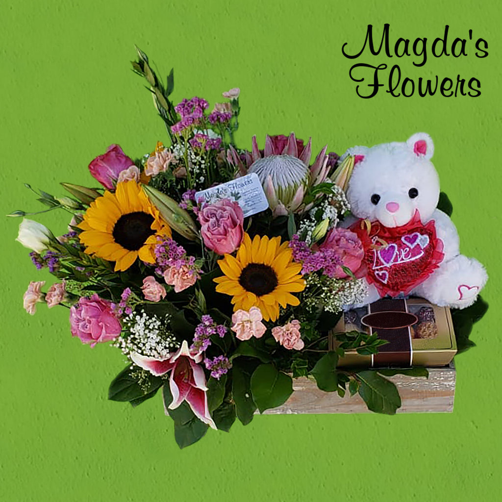 Sunflowers, King Protea, Lilies, Roses, a teddy and more in this beautiful floral arrangement.