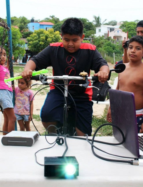 A young man pedals to power a computer and projector