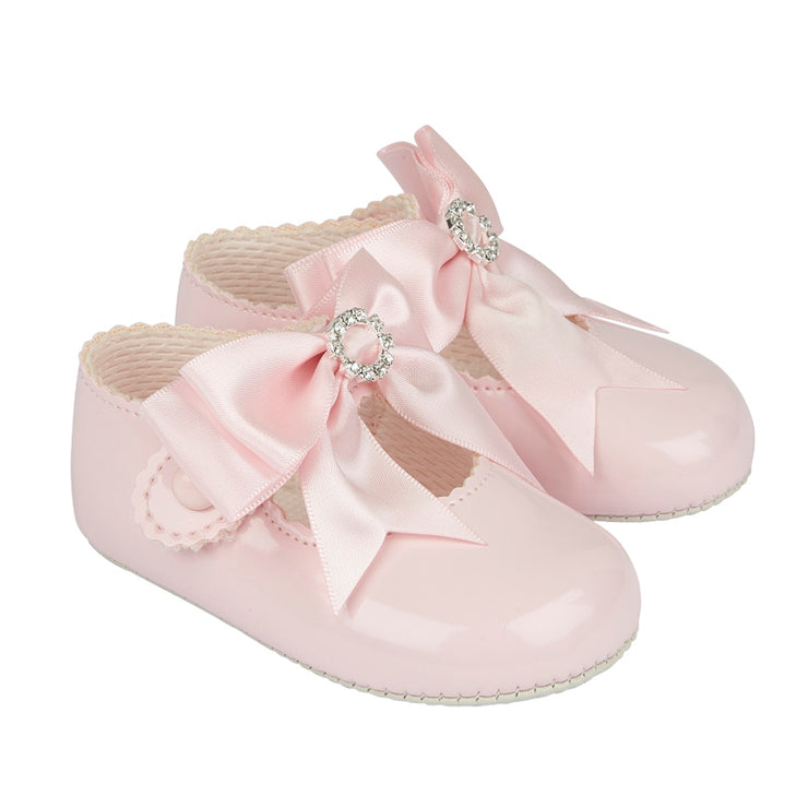 Pink patent shoes with large satin bow and diamanté detail. Gripper sole and button fastening.