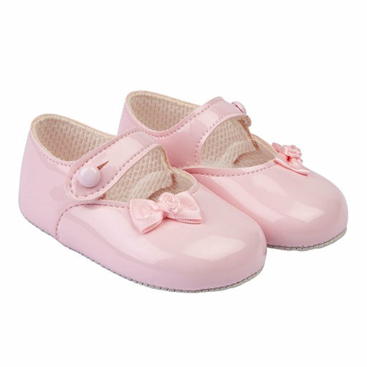 Pink patent shoes with small ribbon bow and flower.  Button bar and gripper sole.