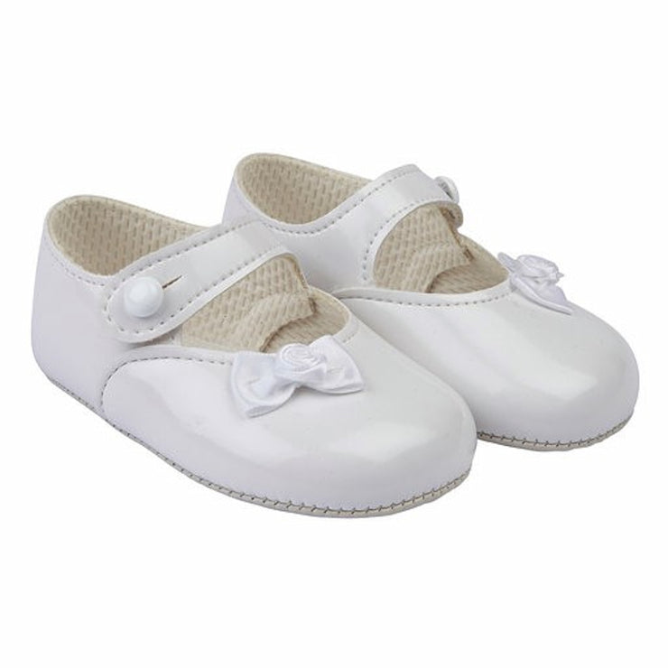 White patent shoes with small ribbon bow and flower. Button bar and gripper sole.