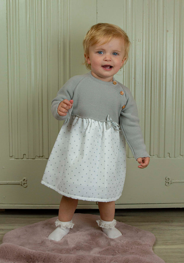This dress has a grey knitted top with wooden buttons to front making it easy to pop on and off over baby's head!. Satin bow to waist, white skirt with grey spots, so comfortable and looks lovely with socks or tights!