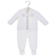 Knitted two-piece suit with pom pom tie to jacket. The trousers have feet to keep baby warm on cooler days!  Available in white, pink and blue.  Why not buy a pom pom hat to finish off the outfit!