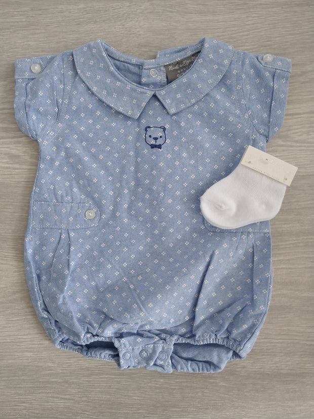 Chambray romper in sky blue and white, with printed teddy bear face to front, comes with pair white ankle socks. Popper fastenings to back and legs.