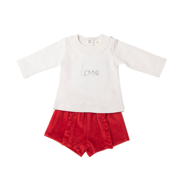 """Love"" top and velour shorts set by Babybol Barcelona.   The ivory coloured top has a pleated collar and ""love"" slogan in diamontes. Poppers to back.  Red velour shorts with frill detail to front of both legs.  Shorts: 92% polyester 8% elastane  Top: 95% cotton 5% elastane"